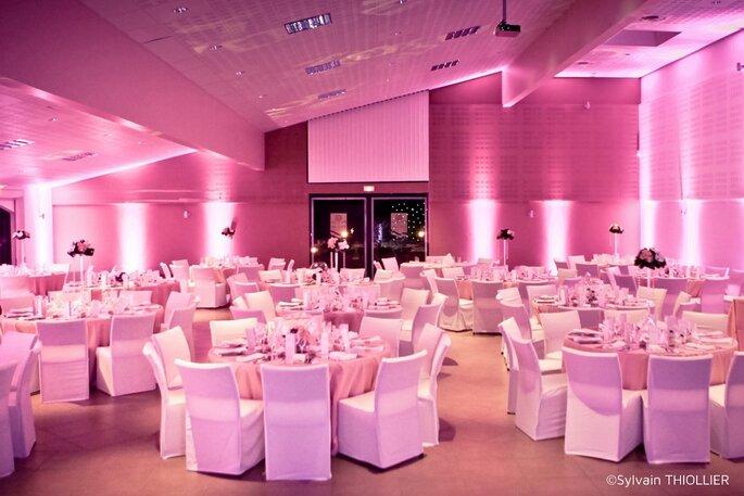 Une salle de réception de mariage prête à recevoir les invités, éclairée de rose