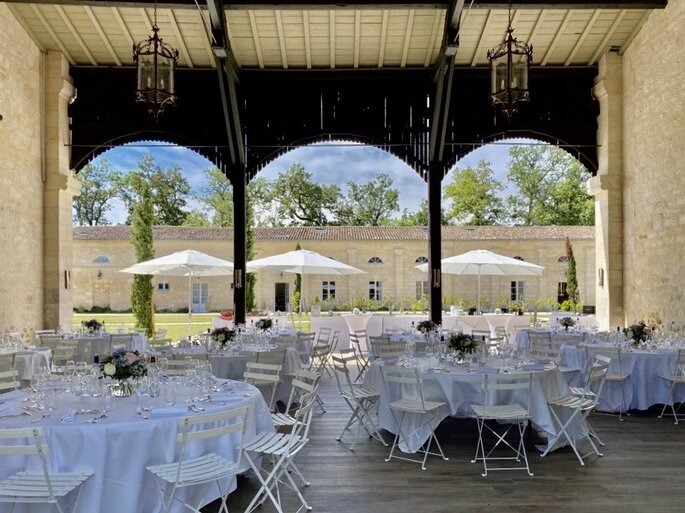 Préau du Château Cassies avec des alcôves en bois, des tables de mariage dressées et un jardin