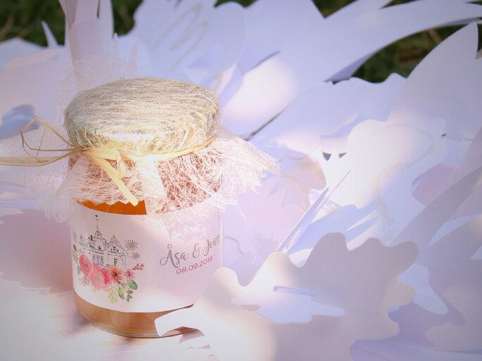 Un pot de miel personnalisé avec une jolie étiquette fleurie disposé sur une table