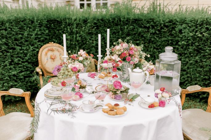 Table ronde décorée et prête pour prendre le thé dans un jardin.