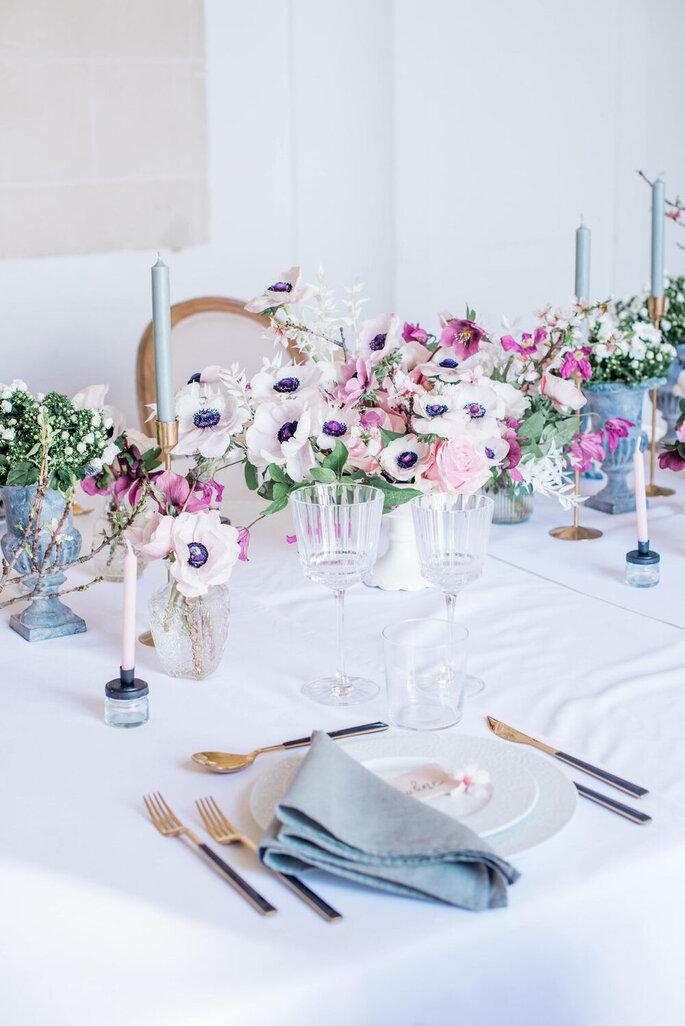 Une table décorée avec des compositions de fleurs roses pour un mariage