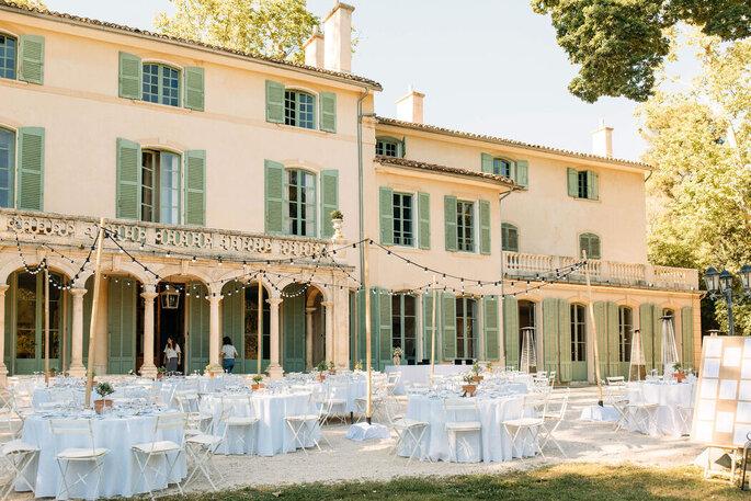 Style guinguette pour une réception en extérieur, tables rondes et lampions, devant une jolie façade aux volets verts