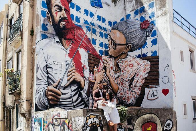 casal sentado em frente a uma parede com grafiti artístico mural arte de rua