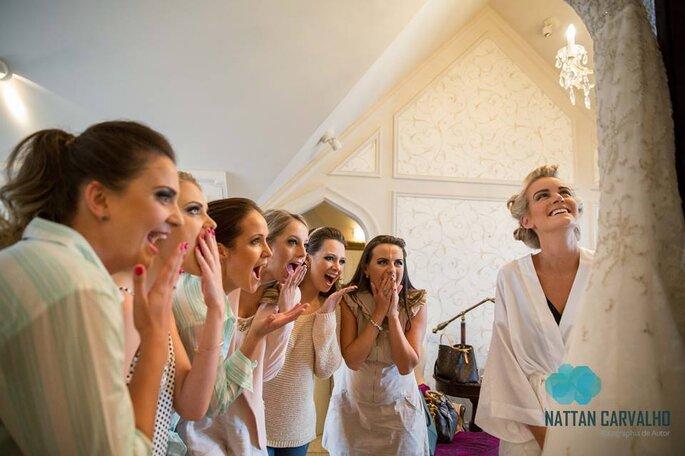 Madrinhas olhando impressionadas para a noiva e seu lindo vestido