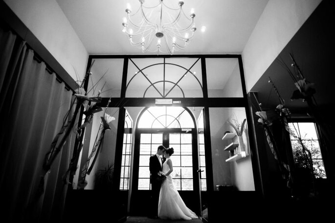 Un couple de mariés enlacés dans la superbe entrée d'un lieu de réception, photo de mariage en noir et blanc