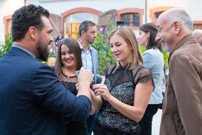 Un tour de carte proposé à une invitée qui semble surprise, pendant le vin d'honneur