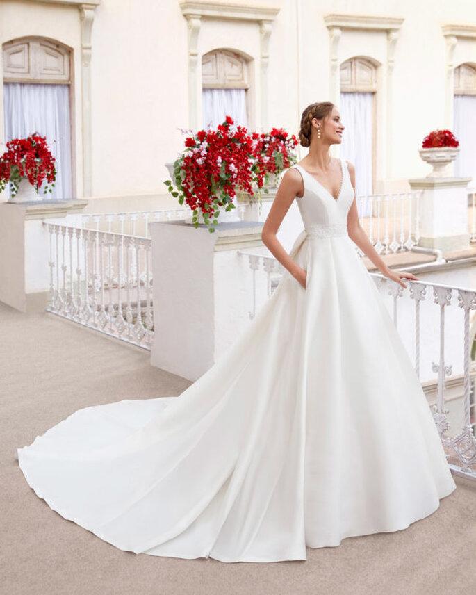 Aire Barcelona Vestidos de novia sencillos vestido de novia corte princesa con escote en V y sencillos tirantes con espalda abierta y voluminosa falda luce con gran lazo y bolsillos.