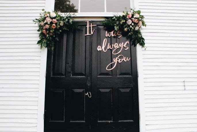 puerta con letrero para boda y arreglo floral