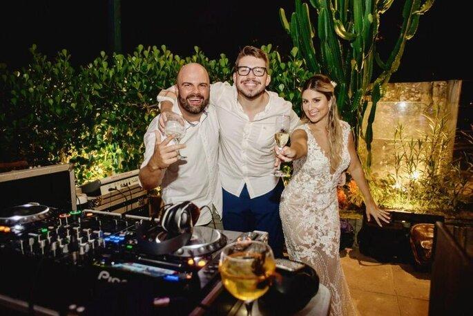 O DJ posa com os noivos durante a festa