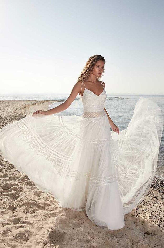 Eine Braut steht in einem Boho-Brautkleid am Strand und schwingt den Rock.
