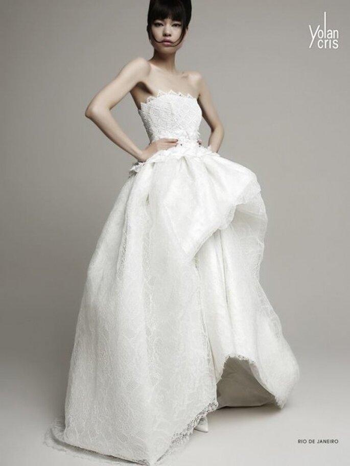 Vestido de novia en color blanco con escote strapless, silueta peplum discreta y acabado asimétrico en la falda - Foto YolanCris