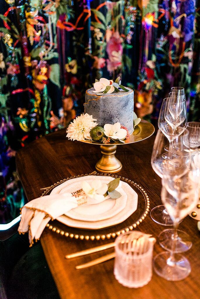 Blick auf den Hochzeitstisch, im Hintergrund ist die Hochzeitstorte von Café Huttenhof zu sehen.