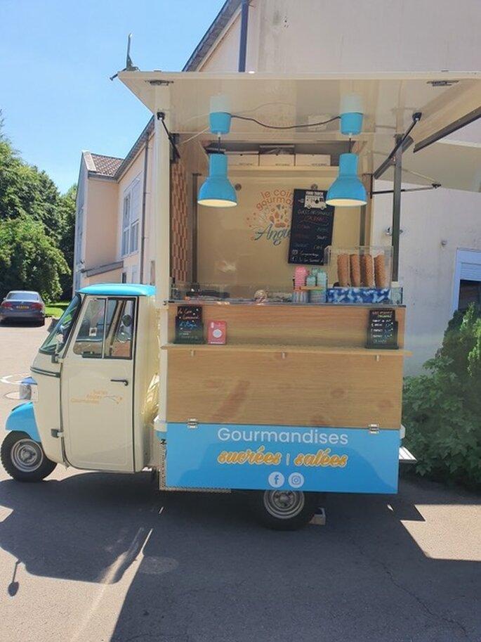 Le food truck d'Angie est aménagé avec du mobilier en bois clair et de la décoration bleue, qui lui donne un côté vintage