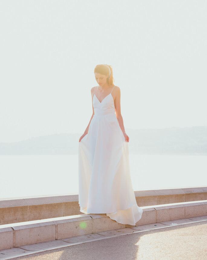 Une mariée portant une robe minimaliste et élégante, debout sur une rambarde, au bord de la mer