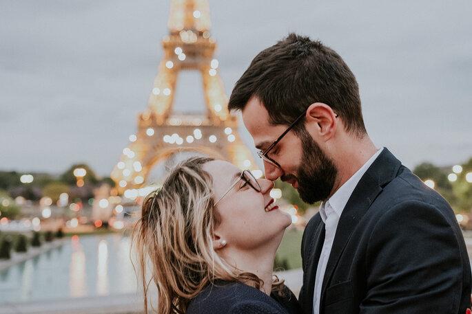 casal de namorados cumplices em frente à torre eiffel paris frança
