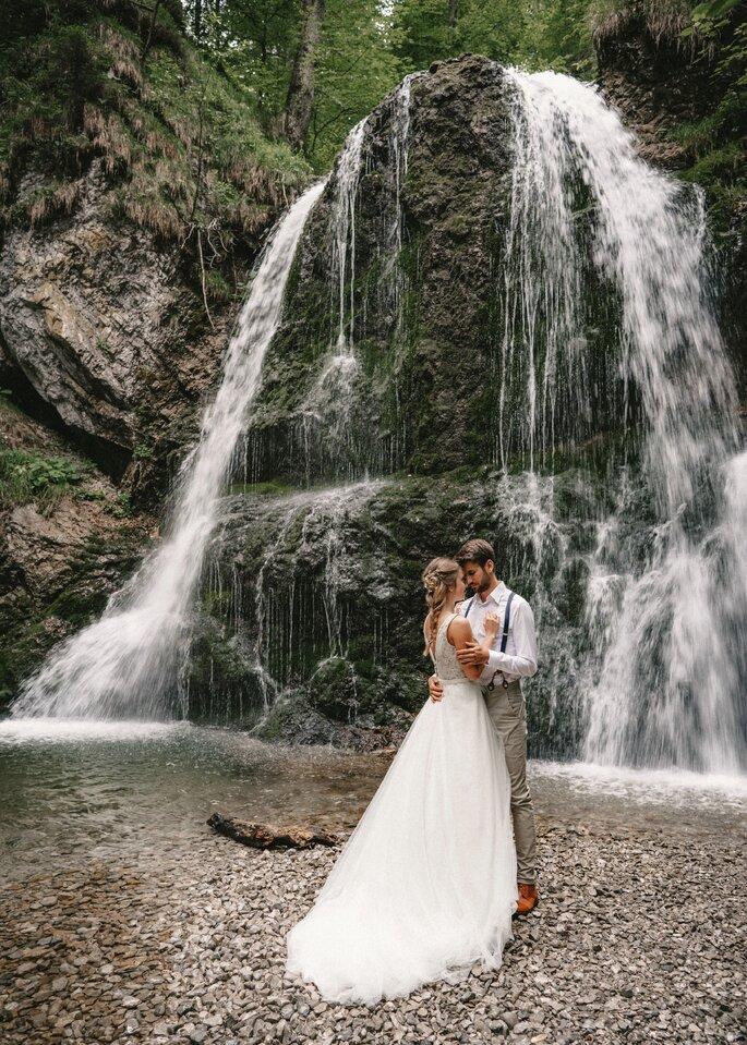 Brautpaar steht sich in den armen haltend vor dem Wasserfall.