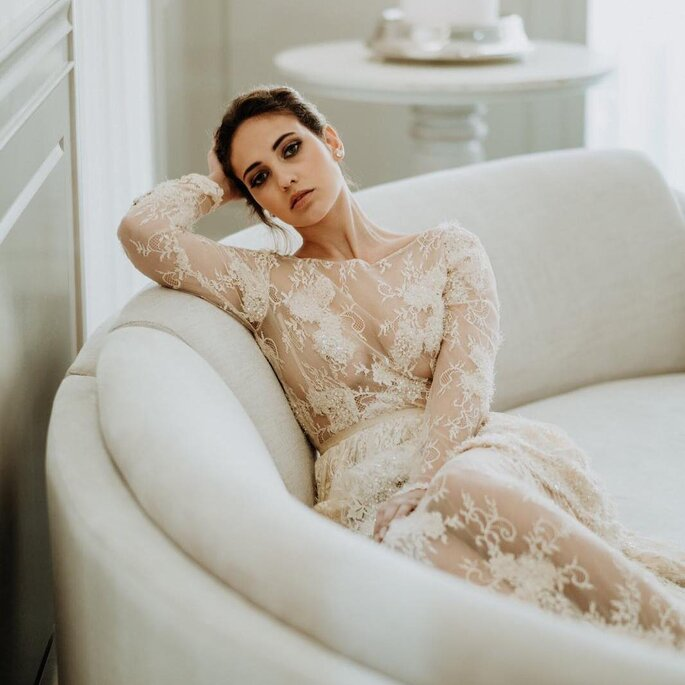 noiva com vestido rendado transparente manga comprida sentada num sofá