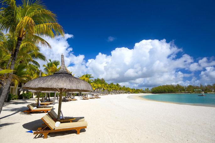 Playa de arena blanca con tumbonas y sombrillas en Isla Mauricio.