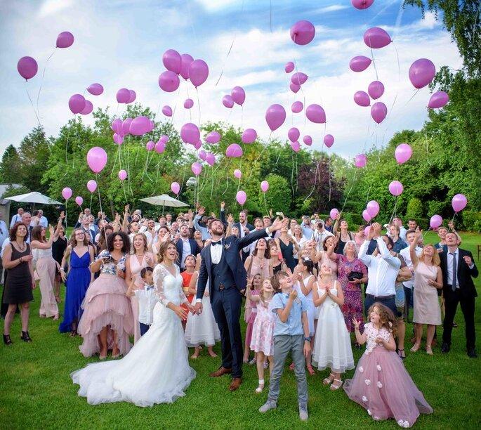 Une photographie de mariage en groupe avec des mariés au milieu de leurs invités laissant des ballons roses s'envoler