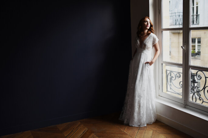 Une robe de mariée longue en dentelle avec un décolleté, un modèle créé par une créatrice de robes de mariée