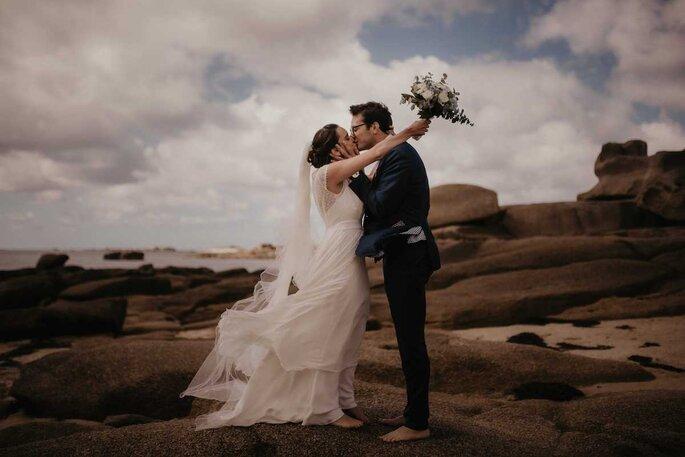 Un couple de mariés s'embrasse dans un paysage rocailleux en bord de mer.