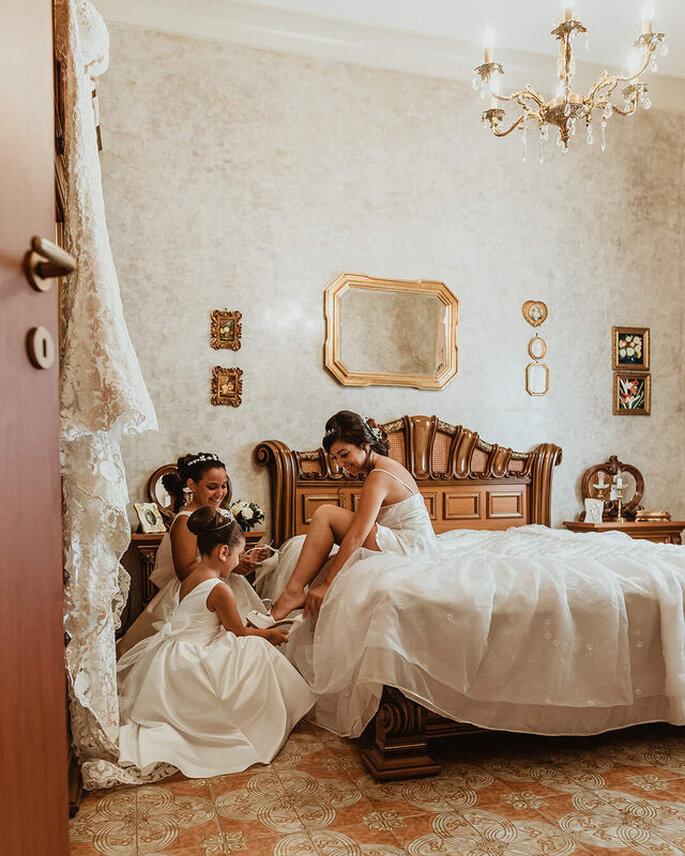 La sposa aiutata dalle damigelle nella preparazione del look