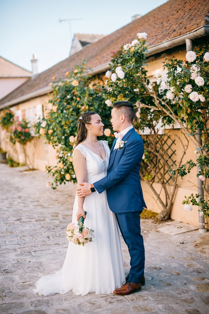 Un couple de mariés enlacé devant une jolie façade ornée de roses trémières