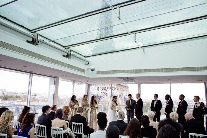 Cérémonie de mariage chic sous une baie vitrée surplombée par la Tour Eiffel