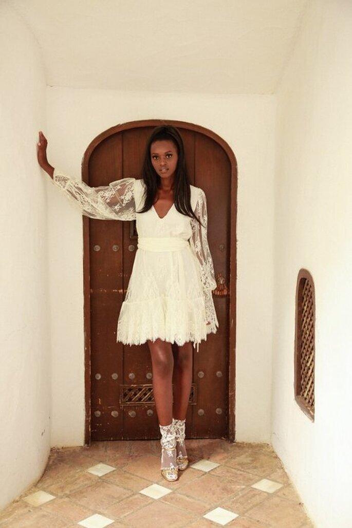 Une mariée portant une robe courte toute en dentelle avec des manches longues transparentes en dentelle