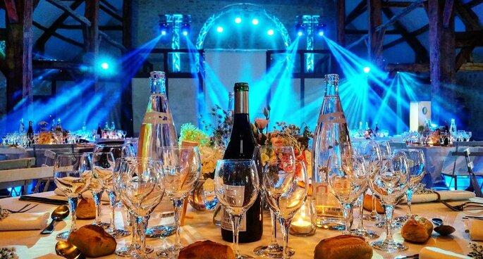 La table de la réception d'un mariage avec les boissons, dans une salle à l'éclairage travaillé
