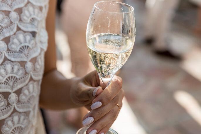 La mariée un verre de chanpagne à la main pour célébrer son grand jour
