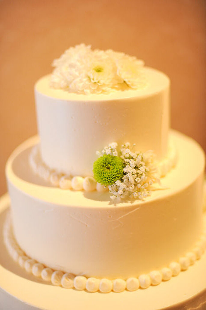 Pastel de boda blanco, redondo a 2 niveles, adornado con flores y detalles verdes