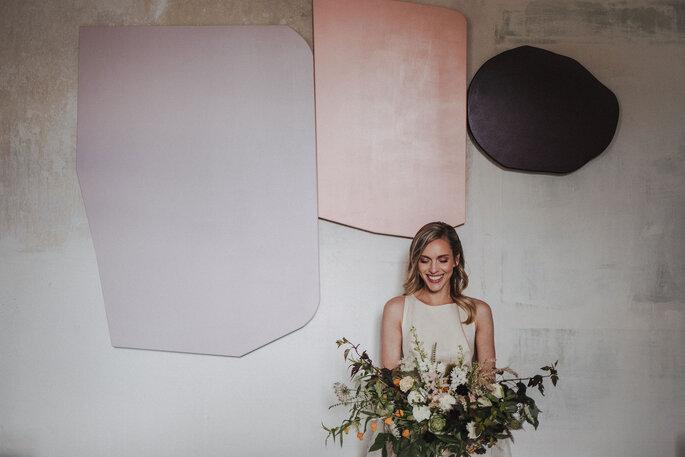 lachende Braut mit Brautstrauß vor bunter Wand