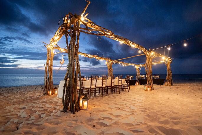 Un dîner se prépare sur la plage, dans une ambiance romantique.