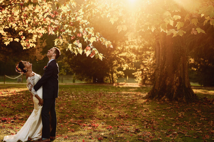 Un couple de mariés enlacé et heureux avec un paysage d'automne en toile de fond