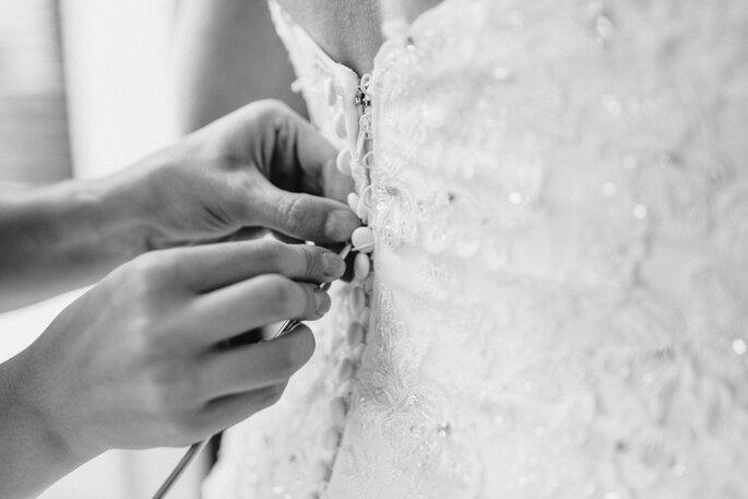 Getting Ready. Brautkleid der Braut wird zugeknöpft