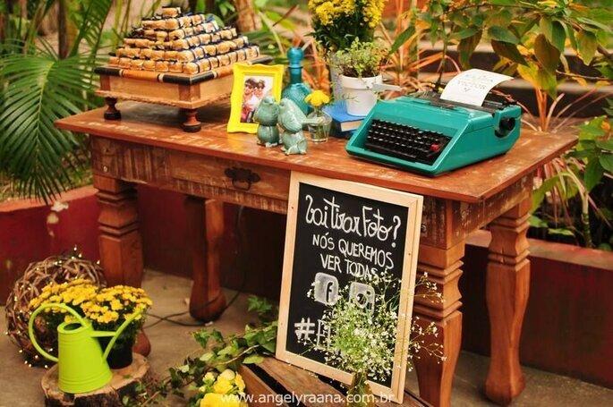 Mesa de bem casados com máquina de escrever, flores e um canto para fotos