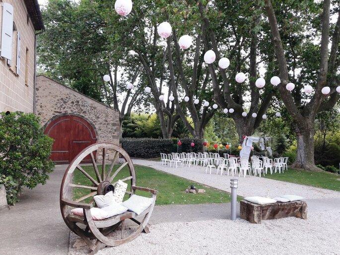 Une cérémonie laïque en extérieur dans un cadre champêtre soigné. Un fauteuil fabriqué à partir d'une roue en bois.
