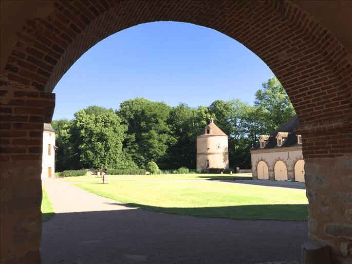 Une photo prise sous le pont levis du domaine, qui montre le parc du château