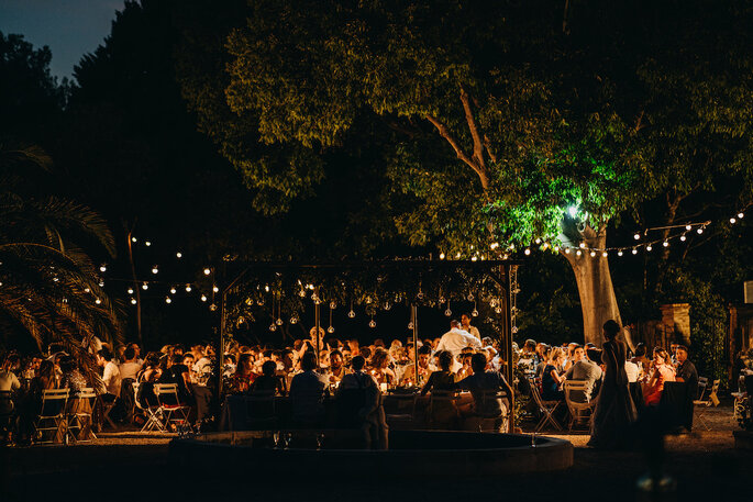 Dîner de mariage en extérieur à la nuit tombée, tables éclairées de lampions, style guinguette