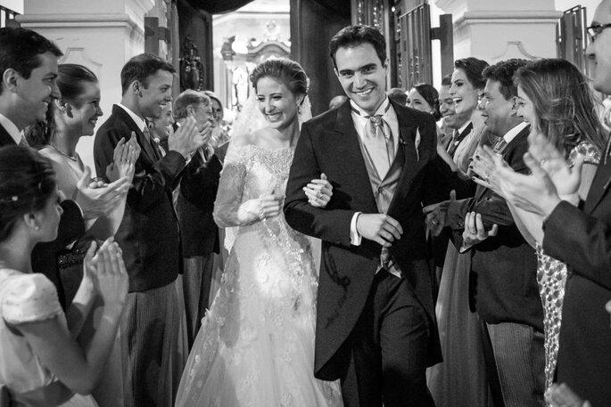Casal de noivos saindo da igreja e cumprimentando os convidados