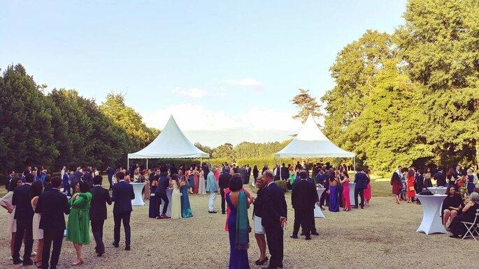 Les invités d'un mariage dans un grand parc arboré, avec des chapiteaux en fond