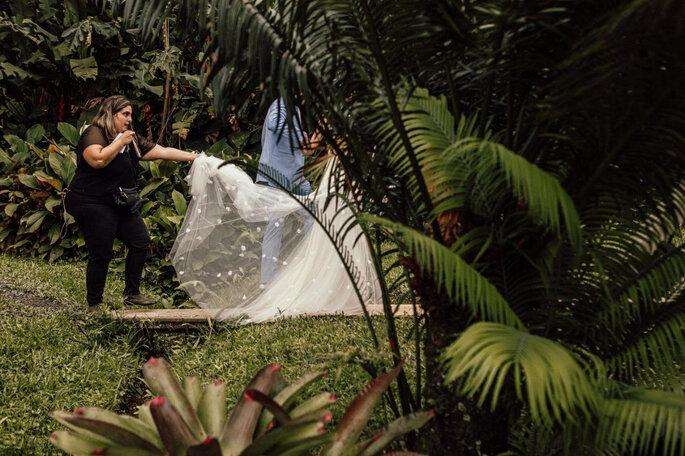 Assessora ajudando a carregar o véu da noiva