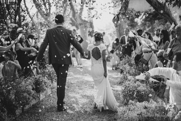 Deux mariés se tenant par la main en train de marcher sous leur haie d'honneur, tandis que leurs invités leur jettent des confettis