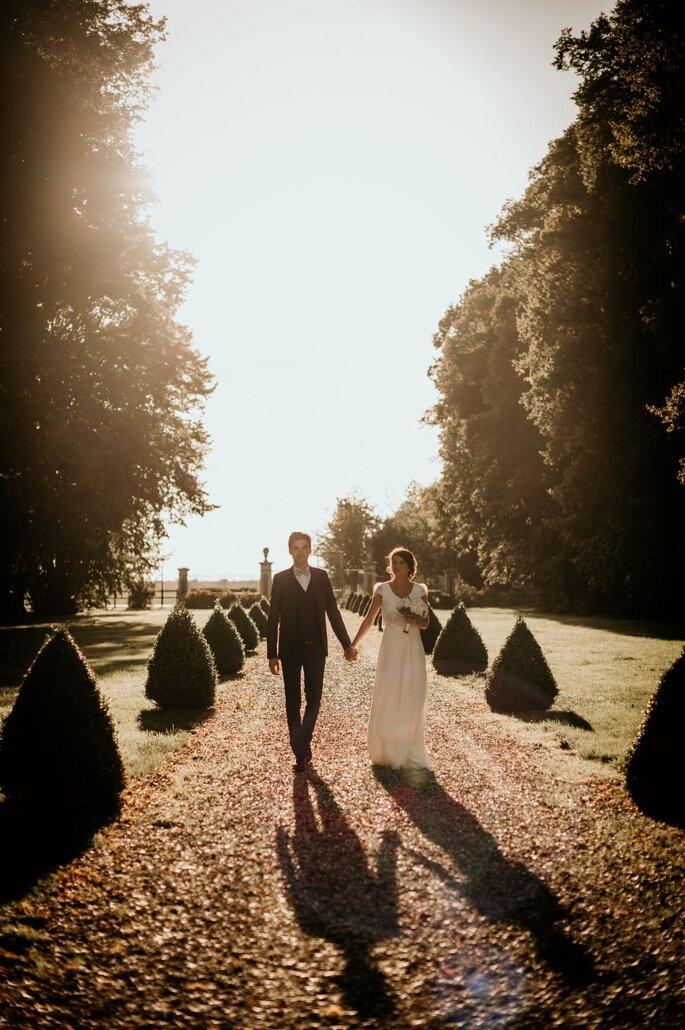 Deux mariés se promènent main dans la main dans une allée