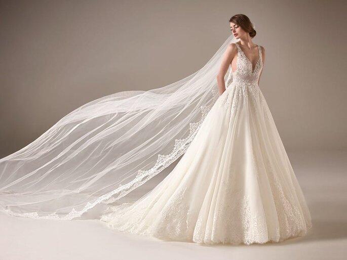 Pronovias vestido de novia en corte princesa Vestido de novia en corte princesa en tejido en tul de encaje con escote de pico, tirantes, y decorado con pétalos de pedrería.