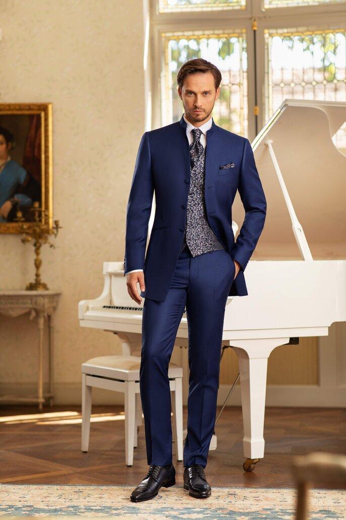 Un marié portant un costume bleu marine très élégant devant un piano à queue.