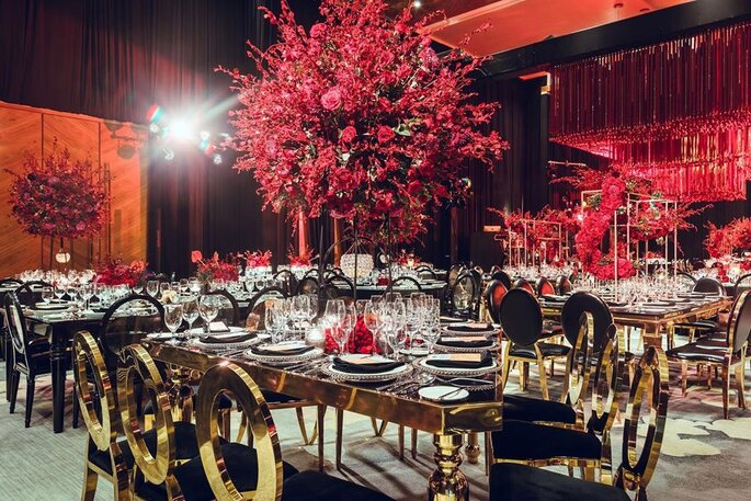 Decoración alta para mesas en colores rojos y sillas negras con dorado