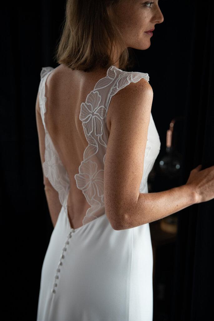 Grand dos-nu d'une robe de mariée et bretelles en dentelles.