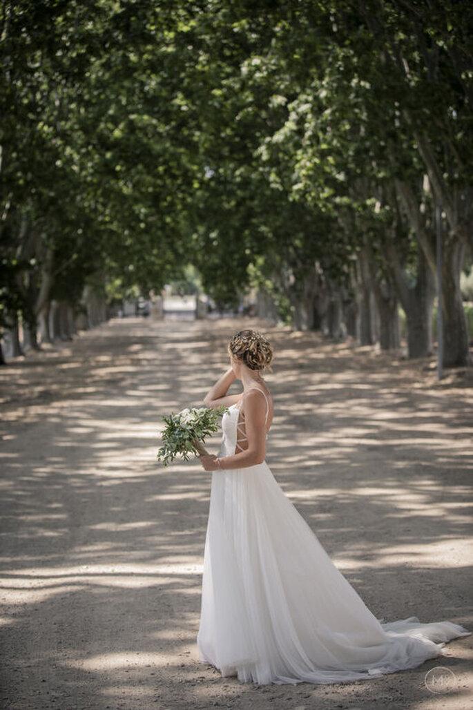 Une mariée, bouquet à la main, regarde au loins dans une allée à l'ombre des arbres.
